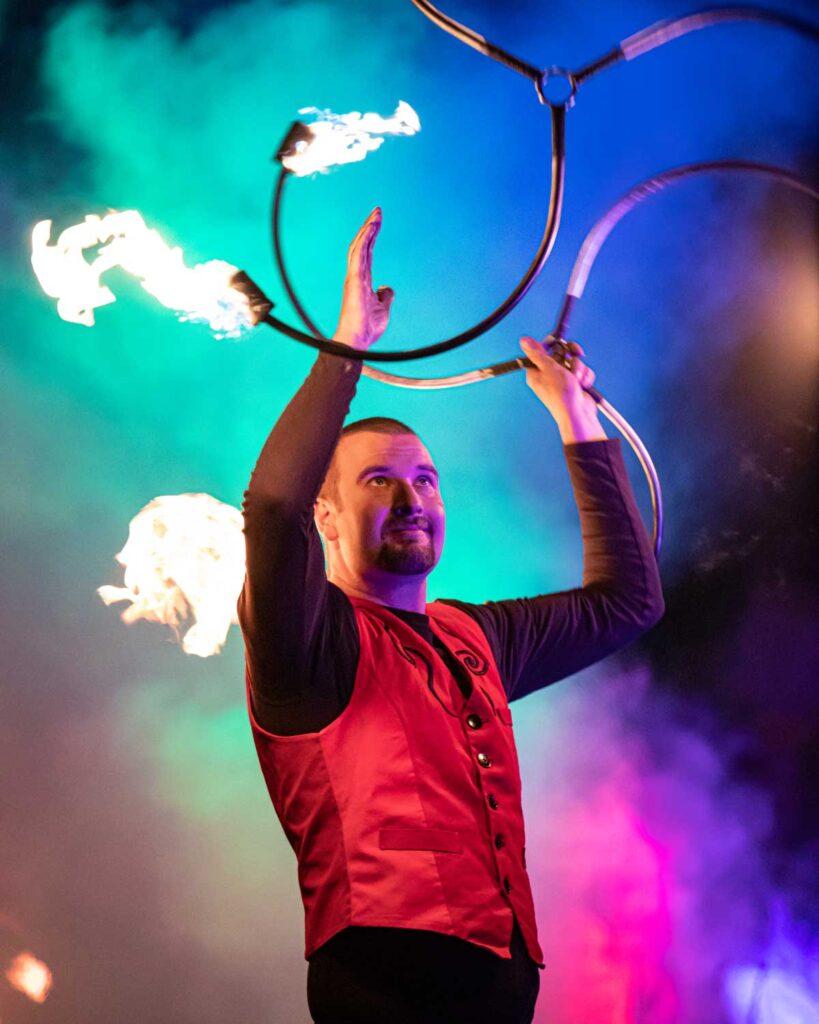 Feuerkünstler zeigt seine Performance bei einer Feuershow im feuerfesten Kostüm