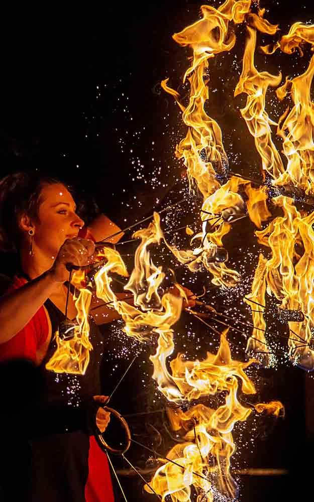 brennende Feuerfächer bei einer Feuershow mit einer Feuerspielerin