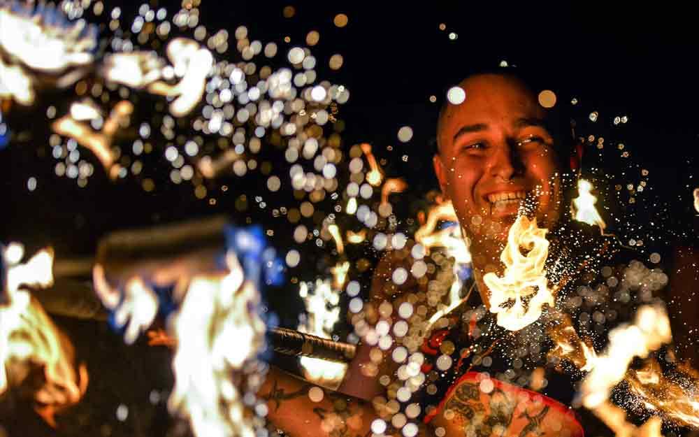 Feuerkünstler und Feuerspucker zeigen ein Lächeln auf der Bühnen